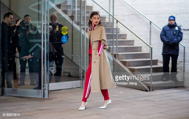 Zendaya wearing trench coat, red track suit, white heels seen outside Michael Kors on February 14, 2018 in New York City.
