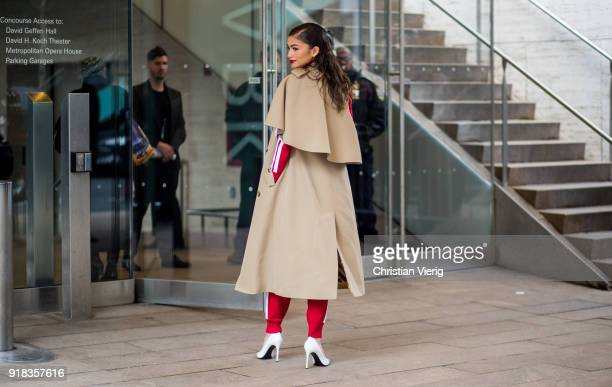 Zendaya wearing trench coat red track suit white heels seen outside Michael Kors on February 14 2018 in New York City