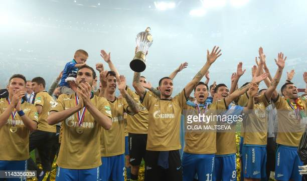 Zenit St Petersburg players pose with a trophy as they celebrate a victory of 2018/19 Russian Premier League after the Round 28 match against CSKA...