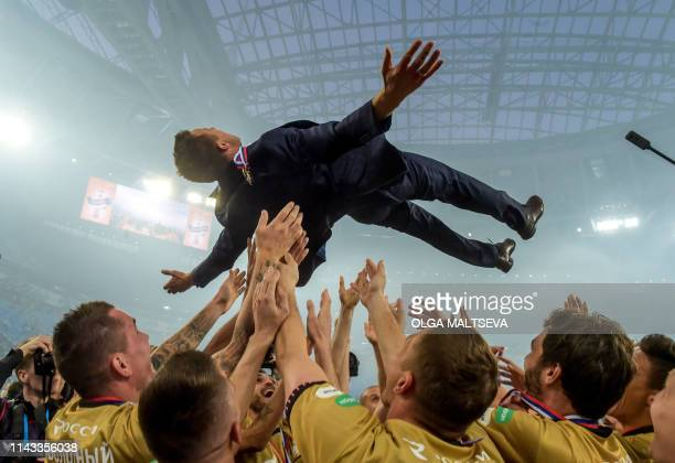 TOPSHOT Zenit St Petersburg players toss up head coach Sergei Semak as they celebrate a victory of 2018/19 Russian Premier League after the Round 28...