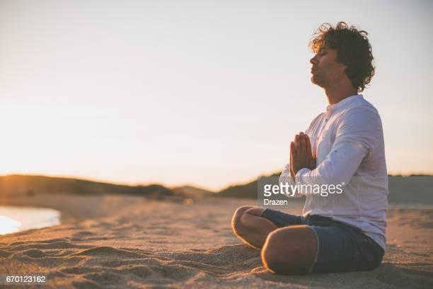 Zen-like position on beach in sunset