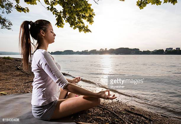 Zen-like woman meditating on the beach in lotus position.