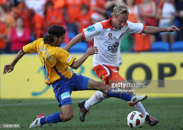Zenon Caravella of the Gold Coast challenges Mitchell Nichols of the Roar during the round one A-League match between Gold Coast United and the...