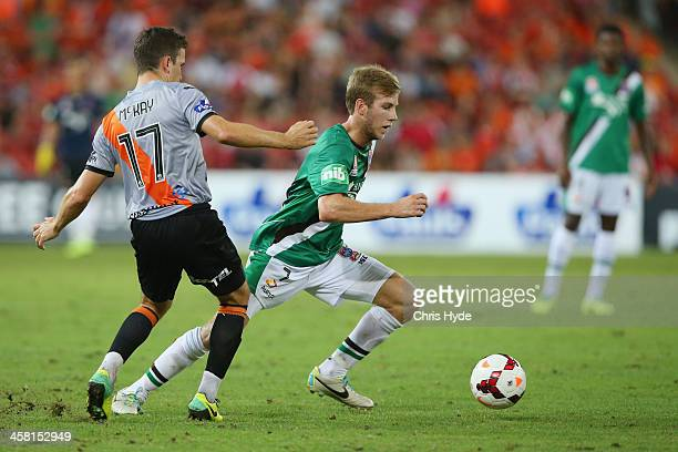 Zenon Caravella of the Jets takes the ball past Matthew McKay of the Roar during the round 11 ALeague match between Brisbane Roar and the Newcastle...