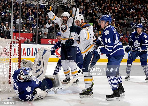 Zenon Konopka and John Scott of the Buffalo Sabres celebrate Matt Ellis' goal against James Reimer and Morgan Rielly of the Toronto Maple Leafs...