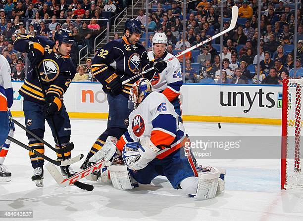 Zenon Konopka and John Scott of the Buffalo Sabres look to deflect a puck that goes past goaltender Anders Nilsson of the New York Islanders on April...