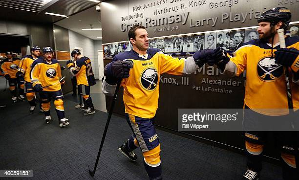 Zenon Konopka of the Buffalo Sabres gets a fist bump from Mike Weber as they head to the ice to warm up for their game against the New Jersey Devils...