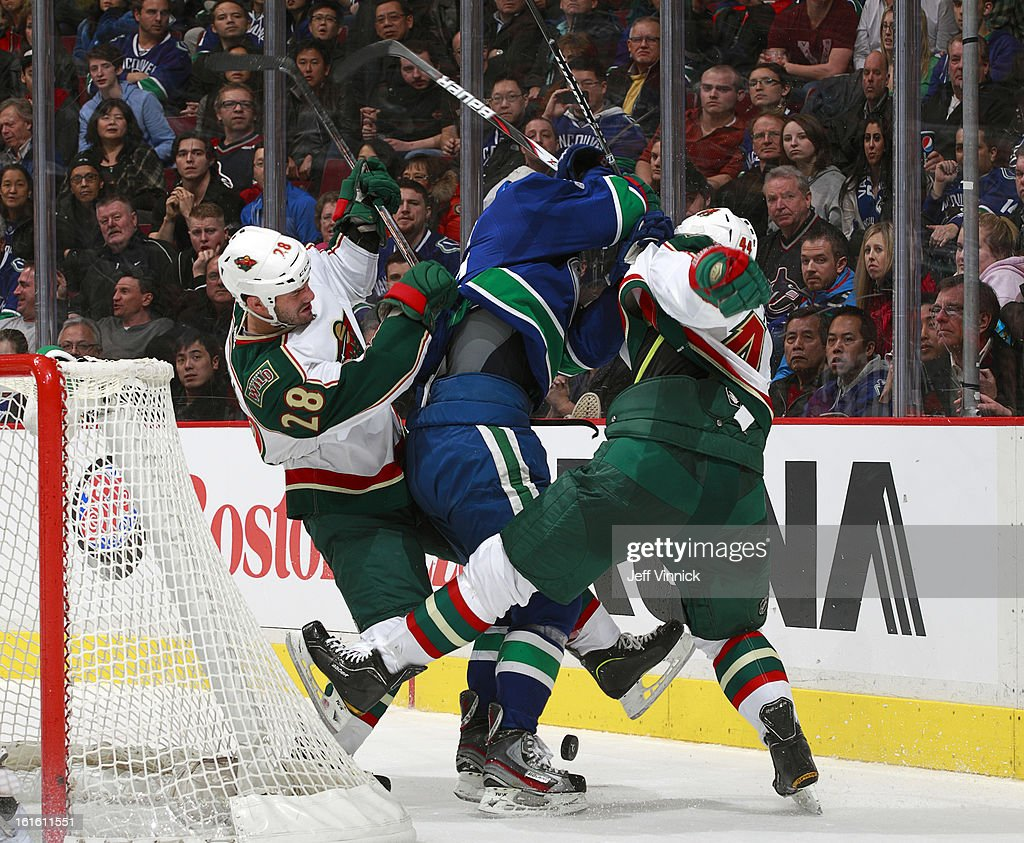 Zenon Konopka #28 of the Minnesota Wild #28 and Justin Falk #44 of the Minnesota Wild check Jannik Hansen #36 of the Vancouver Canucks during their NHL game at Rogers Arena February 12, 2013 in Vancouver, British Columbia, Canada. Vancouver won 2-1
