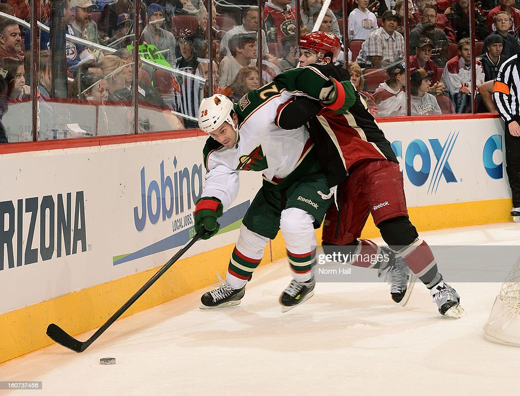 Zenon Konopka #28 of the Minnesota Wild is checked off the puck by Keith Yandle #3 of the Phoenix Coyotes during the third period at Jobing.com Arena on February 4, 2013 in Glendale, Arizona.