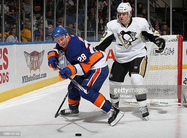 Zenon Konopka of the New York Islanders steals the puck from Ryan Craig of the Pittsburgh Penguins on February 11 2011 at Nassau Coliseum in...