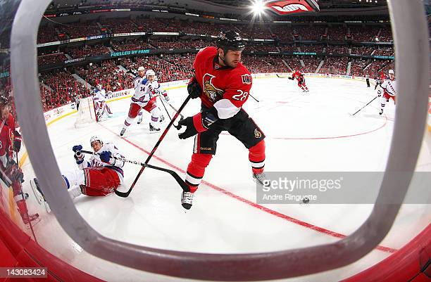 Zenon Konopka of the Ottawa Senators plays the puck after knocking Michael Del Zotto of the New York to the ice in Game Four of the Eastern...
