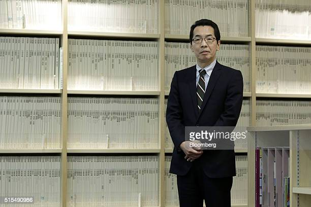Zenshi Takayama president of Zenrin Co poses for a photograph in front of the shelves displaying residential maps at the company's Tokyo head office...