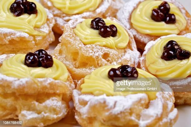 zeppole di san giuseppe (choux pastries filled with cream and amarena, italy) - san giuseppe foto e immagini stock