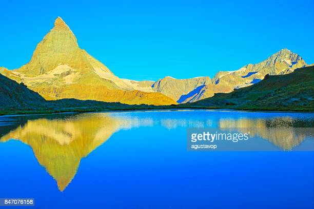 zermatt fairy tale landscape – ethereal matterhorn mirrored lake reflection and gold colored dawn sunrise: idyllic alpine valley and dreamlike dramatic swiss snowcapped national symbol mountain, idyllic countryside, valais canton, swiss alps, switzerland - reflection lake stock photos and pictures
