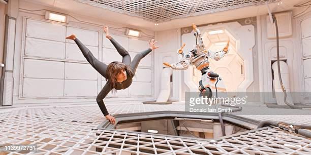 zero g: woman and robot floating adrift inside spaceship - wohngebäude innenansicht stock-fotos und bilder