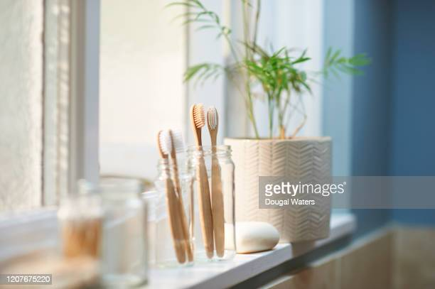 zero waste plastic free products on bathroom window sill. - toothbrush stock pictures, royalty-free photos & images