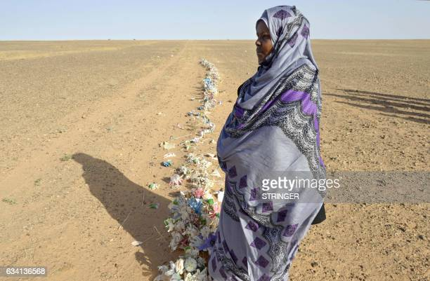Zghala a Saharawi woman stands in front of fake flowers looking at Moroccan soldiers in the AlMahbes area as she accompanies her 14yearold son to...