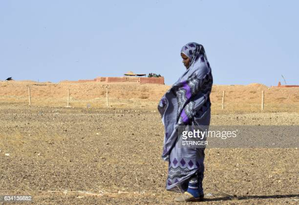 Zghala a Saharawi woman stands near an outlook post of Moroccan soldiers in the AlMahbes area as she accompanies her 14yearold son to show him the...