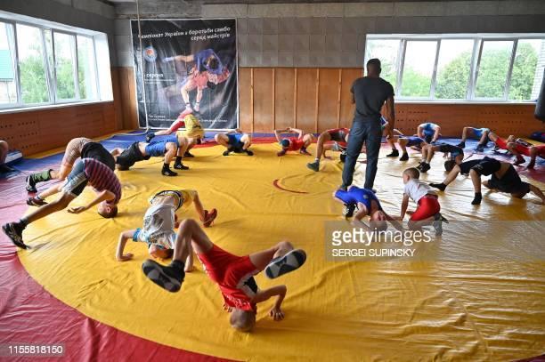 Zhan Beleniuk leads a training of young wrestlers at a sports school for children in Boyarka, near the Ukrainian capital of Kiev, on July 4, 2019. -...
