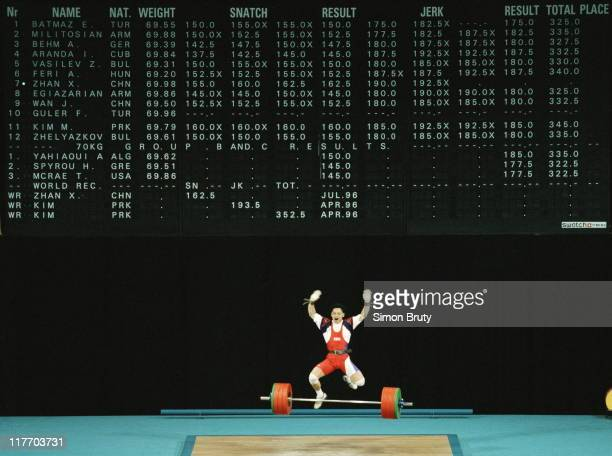 Zhan Xugang of China jumps into the air to celebrate a new world record and winning gold in the Men's Lightweight Weightlifting event on 23rd July...