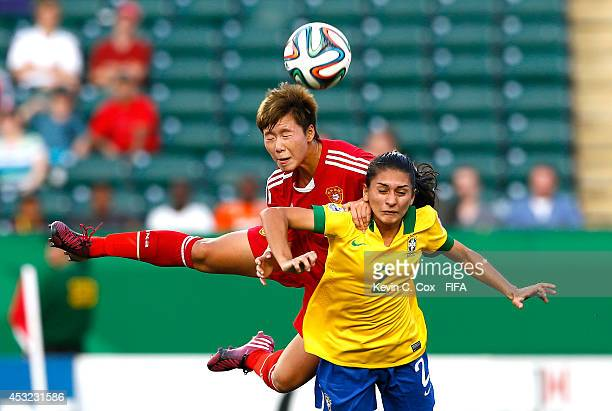 Zhang Chen of China PR attempts a header on goal against Leticia Santos of Brazil at Commonwealth Stadium on August 5 2014 in Edmonton Canada
