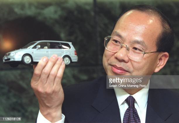 Zhang Fangyou chairman of Denway Motors displays a model of the new Honda vehicle during the company's annual results briefing on April 11 2002 Zhang...