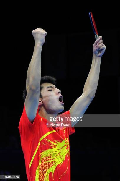 Zhang Jike celebrates defeating Seungmin Ryu and Sang Eun Oh of Korea 3-0 with playing partner Wang Hao of China and winning the Men's Team Table...