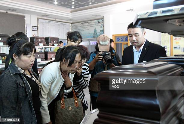 Zhang Jing chooses a box to hold the ashes of her husband Xia Junfeng a 36yearold street vendor at Dongling Funeral Home on September 26 2013 in...