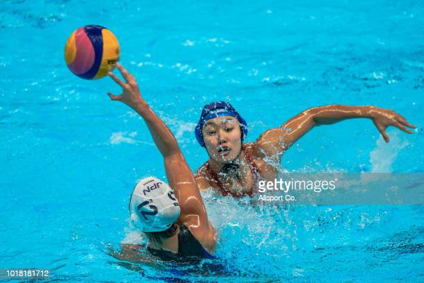 Zhang Jing of China battles Suzuki Katori of Japan during the 18th Asian Games Women's Water Polo preliminary round match between Japan and China at...