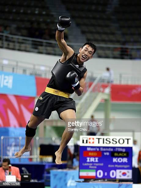 Zhang Kun of China celebrates as he defeats Yoo Sanghoon of South Korea during the Men's Sanda-70kg Wushu Final during day five of the 2014 Asian...
