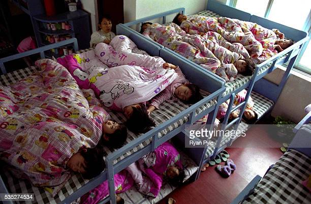 Zhang MengHan and other children prepare for their afternoon sleep on bunk beds at the Li Xiaoshuang Gymnastics School in Xiantao China Li Xiaoshuang...