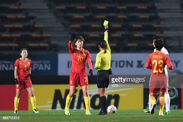 Zhang Rui of China receives a yellow card from the referee during the EAFF E1 Women's Football Championship between China and North Korea at Fukuda...