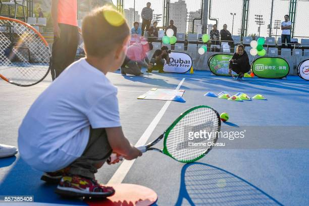 Zhang Shuai of China plays a game with a kid during the Iqiyi kids day on day five of the 2017 China Open at the China National Tennis Centre on...