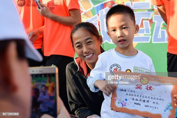 Zhang Shuai of China poses for a picture with a kid during the Iqiyi kids day on day five of the 2017 China Open at the China National Tennis Centre...