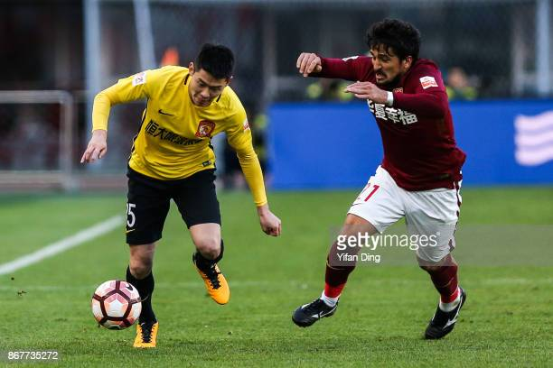 Zhang Wenzhao of Guangzhou Evergrande dribbles past Aloisio dos Santos of Hebei China Fortune during the Chinese Super League match between Hebei...