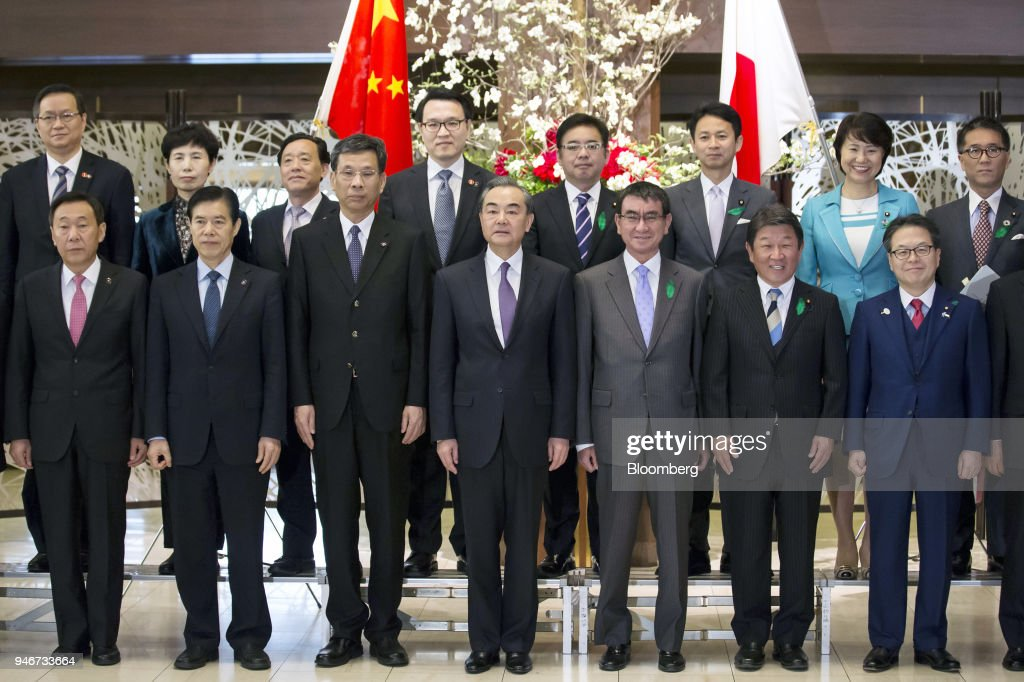 Zhang Yong, vice director of China's National Development and Reform Commission, front row from left to right, Zhong Shan, China's commerce minister, Liu Kun, China's finance minister, Wang Yi, China's foreign minister, Taro Kono, Japan's foreign minister, Toshimitsu Motegi, Japan's economy minister, and Hiroshige Seko, Japan's economy, trade and industry minister, pose for a photograph ahead of a high-level Japan-China economic dialogue in Tokyo, Japan, on Monday, April 16, 2018. The foreign ministers of China and Japan agreed to work closely to push North Korea to abandon its nuclear program, in the latest sign of improved cooperation between Asia's two largest economies. Photographer: Tomohiro Ohsumi/Bloomberg via Getty Images
