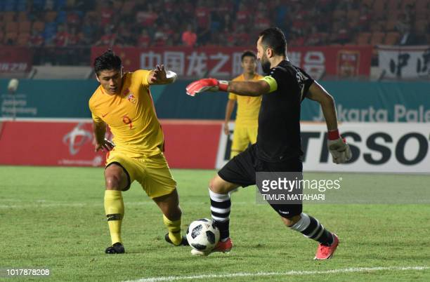 Zhang Yuning of China vies for a ball with Ahmad Madnya of Syria during the men's football preliminary group C match between Syria and China of the...