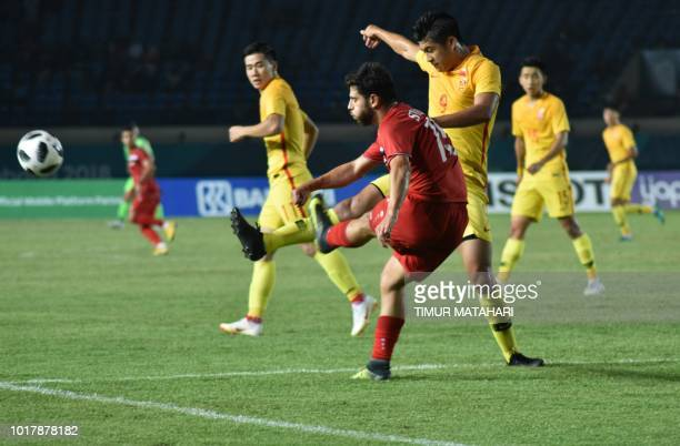 Zhang Yuning of China vies for a ball with Khaled Kurdaghli of Syria of Syria during the men's football preliminary group C match between Syria and...