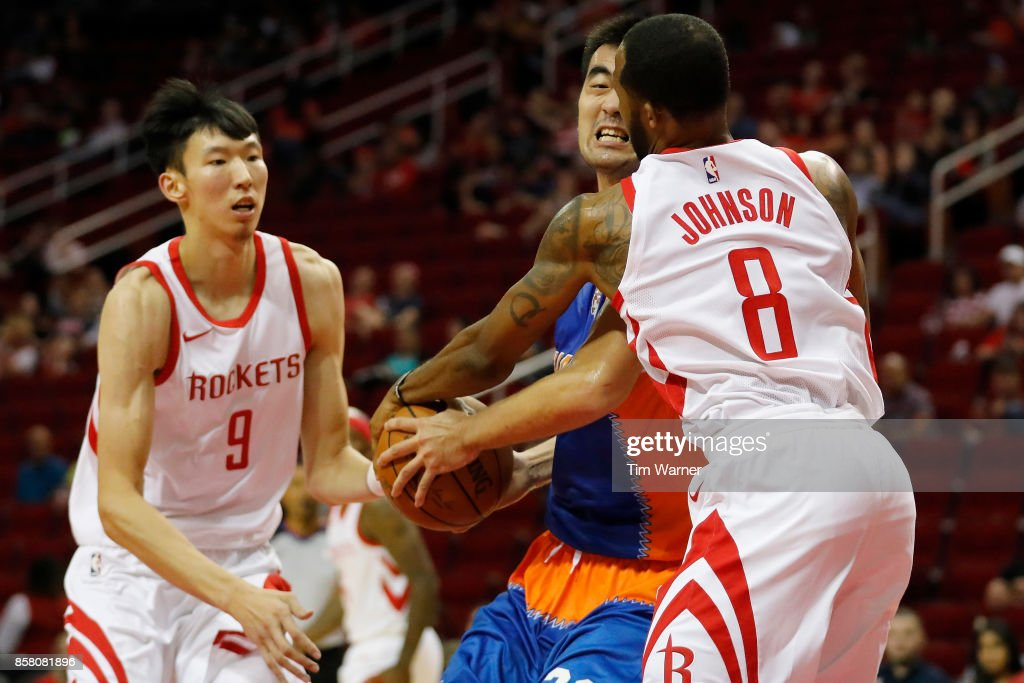 Zhang Zhaoxu #23 of Shanghai Sharks is fouled by Chris Johnson #8 of Houston Rockets in the second half at Toyota Center on October 5, 2017 in Houston, Texas.