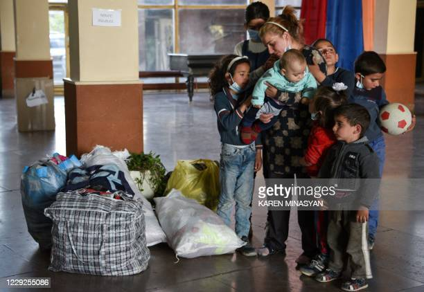 Zhanna Petrosyan , refugee from the village of Tsapatagh of the Nagorno-Karabakh region and her 7 children stand next to their belongings in a centre...