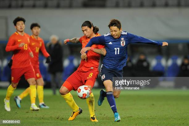 Zhao Yuhao of China and Yu Kobayashi of Japan compete for the ball during the EAFF E1 Men's Football Championship between Japan and China at...