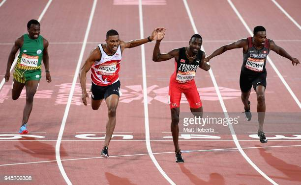 Zharnel Hughes of England crosses the line to win gold ahead of Jereem Richards of Trinidad and Tobago and Aaron Brown of Canada in the Men's 200...