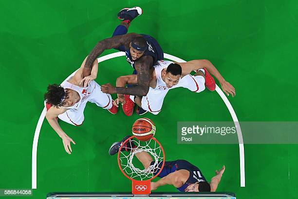 Zhelin Wang and Jianlian Yi go for the rebound against Klay Thompson and Demarcus Cousins of United States in the Men's Preliminary Round Group A...