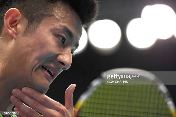 Zhen Long of China wipes his perspiration during his men's singles quarterfinal match against Prannoy HS of India at the Indonesia Open badminton...