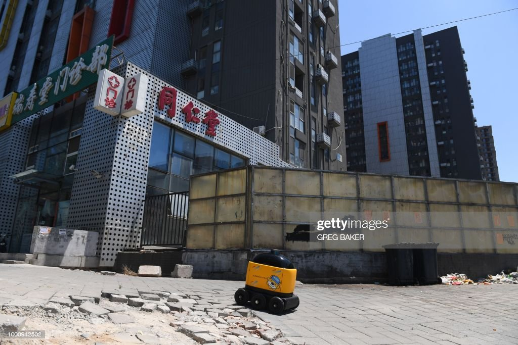 A Zhen Robotics delivery robot makes its way from a Suning supermarket to a residential compound during a demonstration of the robot in Beijing. - Along a quiet residential street on the outer edges of Beijing, a yellow and black cube about the size of a small washing machine trundles leisurely to its destination. This 'little yellow horse' is an autonomous delivery robot, ferrying daily essentials like drinks, fruit and snacks from the local store to the residents of the 'Kafka' compound in the Chinese capital. (Photo by GREG BAKER / AFP) / TO
