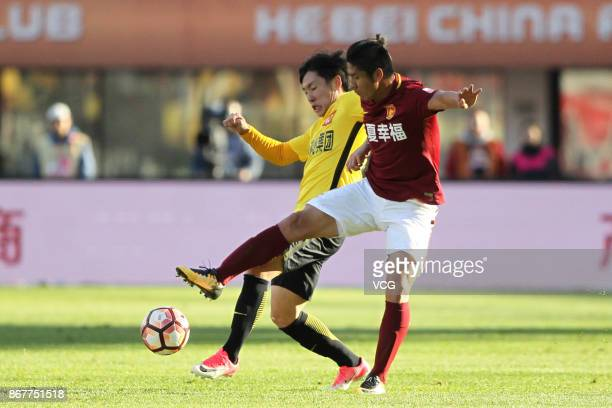 Zheng Long of Guangzhou Evergrande and Zhao Mingjian of Hebei China Fortune compete for ball during the Chinese Super League match between Hebei...
