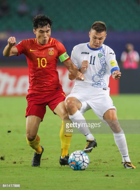 Zheng Zhi of China and Igor Sergeev of Uzbekistan compete for the ball during the 2018 FIFA World Cup qualifier game between China and Uzbekistan at...