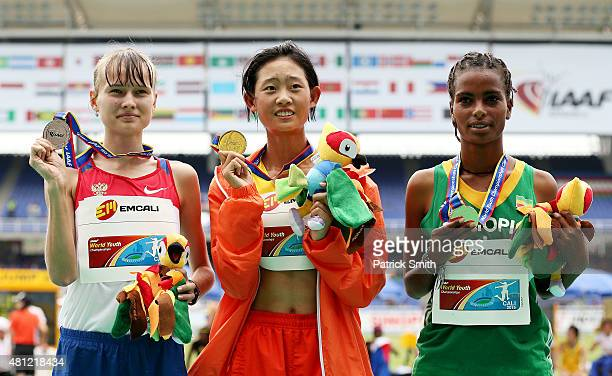 Zhenxia Ma of China gold medal Olga Eliseeva of Russia silver medal and Ayalnesh Dejene of Ethiopia bronze medal celebrate on the podium after...