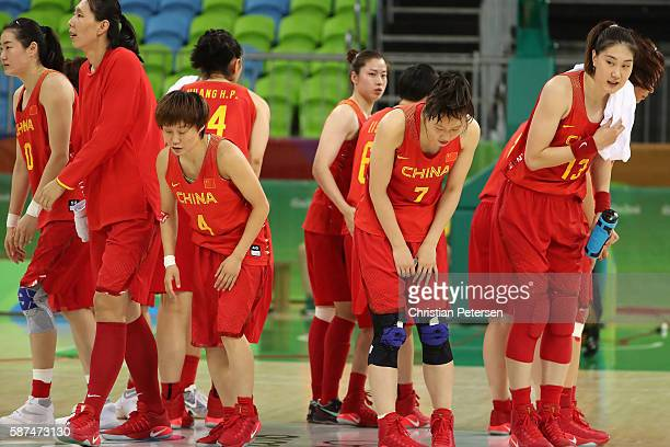 Zhifang Zhao and Ting Shao of China salute the fans after defeating Senegal in the women's basketball game on Day 3 of the Rio 2016 Olympic Games at...