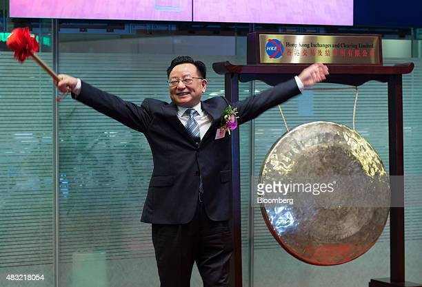 Zhiliang Zhou chairman of China Railway Signal Communication Corp poses after striking a gong during the company's listing ceremony at the Hong Kong...